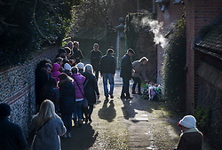 © Licensed to London News Pictures. 26/12/2016. Goring-, UK. Fans of George Michael gather to look at floral tributes placed by his front door (R). Pop superstar George Michael died on Christmas day at his Oxfordshire home on the River Thames aged 53. Photo credit: Peter Macdiarmid/LNP
