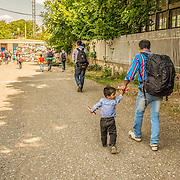 "After registering at the ""one stop"" camp set up by the Serbian Commissariat for Refugees and Migration in the town of Presevo, near the the country's border with Macedonia, a Syrian father and son make their way to the train station to travel northward to Hungary."