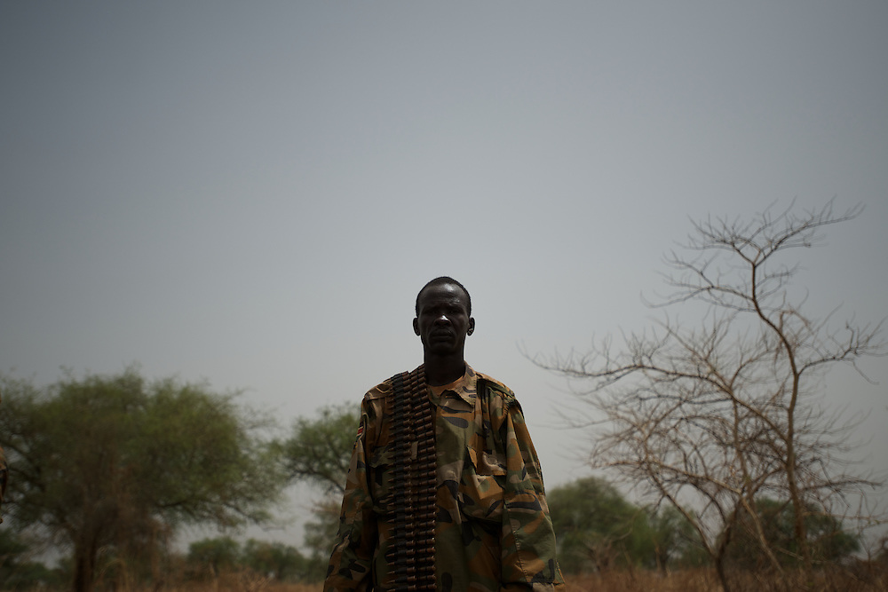 April 24, 2012 - Lalop, South Sudan: A SPLA soldier stands by the location where a bomb as been dropped by Sudan's army airplanes, in the outskirts of a newly established military base in the village o Lalop, 50 kilometers north of Bentiu...South Sudan and their northern neighbors, Sudan, have in the past two weeks been involved in heavily clashes over border disputes. Bentiu and neighboring villages have been under constant bombardment by the troops os Karthoum , who established their positions around 10 kilometers into South Sudan's territory. The international community is concerned about the possibility of a full on war between the two countries. (Paulo Nunes dos Santos/Polaris)