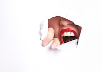 Close-up of furious young woman with red lips trying to break free from paper wall