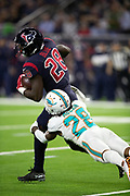 Houston Texans running back Lamar Miller (26) gets tackled from behind by diving Miami Dolphins cornerback Bobby McCain (28) as he runs for a second quarter gain of 12 yards and a first down at the Texans 26 yard line during the NFL week 8 regular season football game against the Miami Dolphins on Thursday, Oct. 25, 2018 in Houston. The Texans won the game 42-23. (©Paul Anthony Spinelli)
