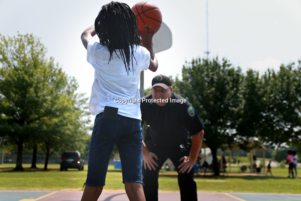 11-year-old Mariah Burnes plays a pickup game of basketball with Tupelo police officer Roy Noe at the Love More Hate Never community prayer gathering at Theron Nickols park Saturday.