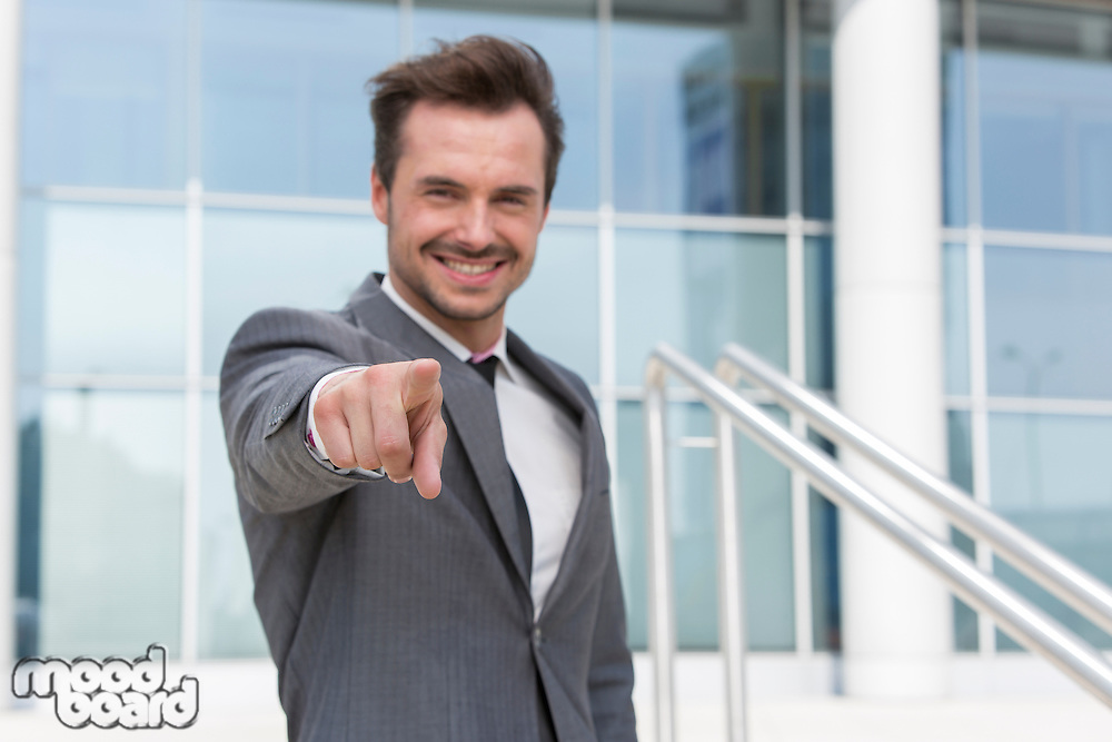 Portrait of confident businessman pointing at you outside office building