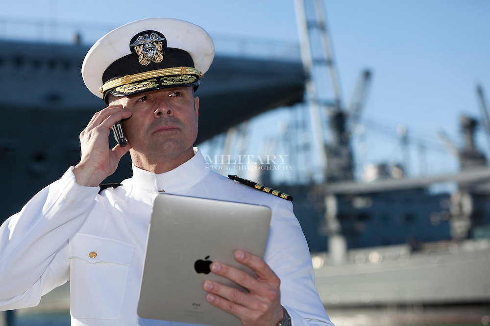 US Navy officer wearing uniform of O-6 Captain uses cell phone and/or Apple iPad.