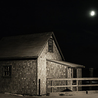 Full moon shines on moody coastal shanty.