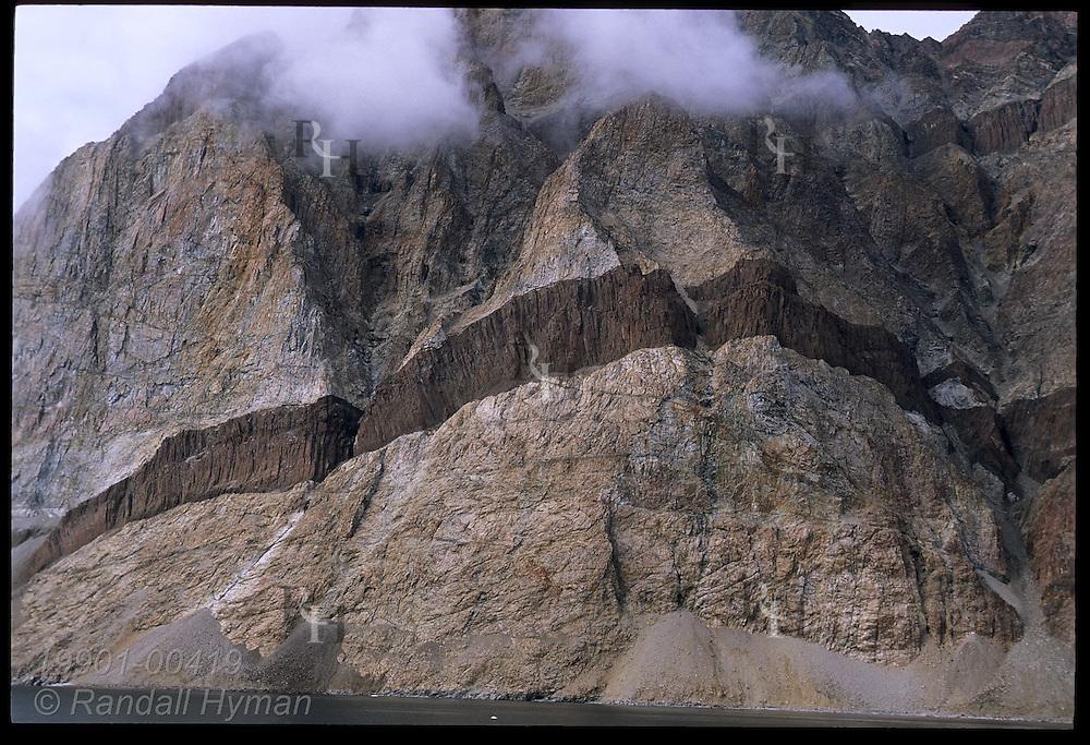 Igneous dike slashes across gneiss mountain, vestige of continental rift that opened N Atlantic 58M yrs ago; Uummannaq Greenland