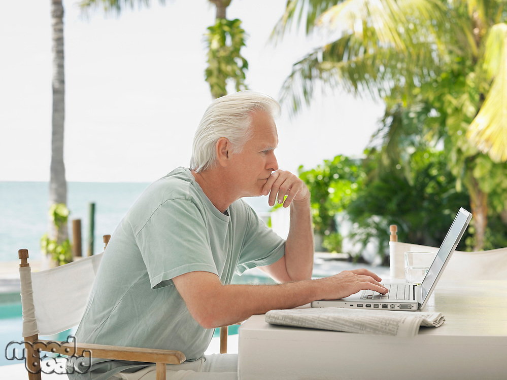Man using laptop at outdoor table side view