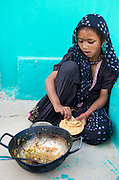 Girl in traditional Rajasthani dress, eating her food in front of a bright green wall.