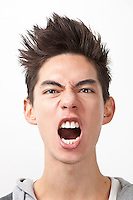 Angry young man screaming against white background
