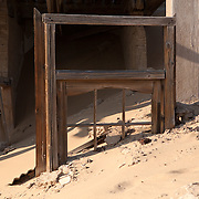 A window frame sits buried in deep sand as part of an abandoned house, in Kolmanskop, Namibia