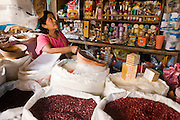 09 JANUARY 2007 - GRANADA, NICARAGUA: A shop keeper in Granada, Nicaragua weighs beans for a customer. Granada, founded in 1524, is one of the oldest cities in the Americas. Granada was relatively untouched by either the Nicaraguan revolution or the Contra War, so its colonial architecture survived relatively unscathed. It has emerged as the heart of Nicaragua's tourism revival.  PHOTO BY JACK KURTZ