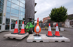 "© Licensed to London News Pictures.  01/07/2018; Bristol, UK. Gromit Unleashed 2. The ""Oh Bollards"" Feathers McGraw character (disguised as a traffic cone) is installed outside Aardman Animations at Bristol Harbourside for the Gromit Unleashed 2 sculpture trail. Gromit Unleashed 2 which officially begins on 02 July will see the Academy Award®-winning character Gromit by Nick Park at Aardman Animations returning to Bristol in 2018 for the second time on sculpture trails to raise money for  the Grand Appeal charity. The character of Gromit will be joined by Wallace and their arch nemesis Feathers McGraw. The trail will feature over 60 giant sculptures designed by high-profile artists, designers, innovators and local talent. Sculptures will be positioned in high footfall and iconic locations around Bristol and the surrounding area. Photo credit: Simon Chapman/LNP"