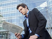 Mid-adult businessman reading newspaper in front of office building