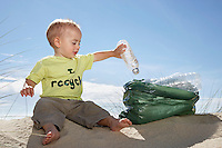 Boy (1-2) playing with plastic bottles on sand dune