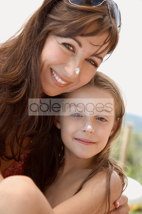 Portrait of mother and daughter embracing with sunscreen lotion on nose
