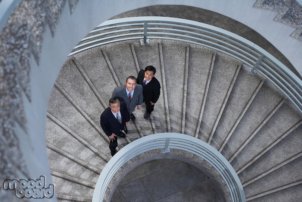 Three business associates standing on spiral staircase portrait