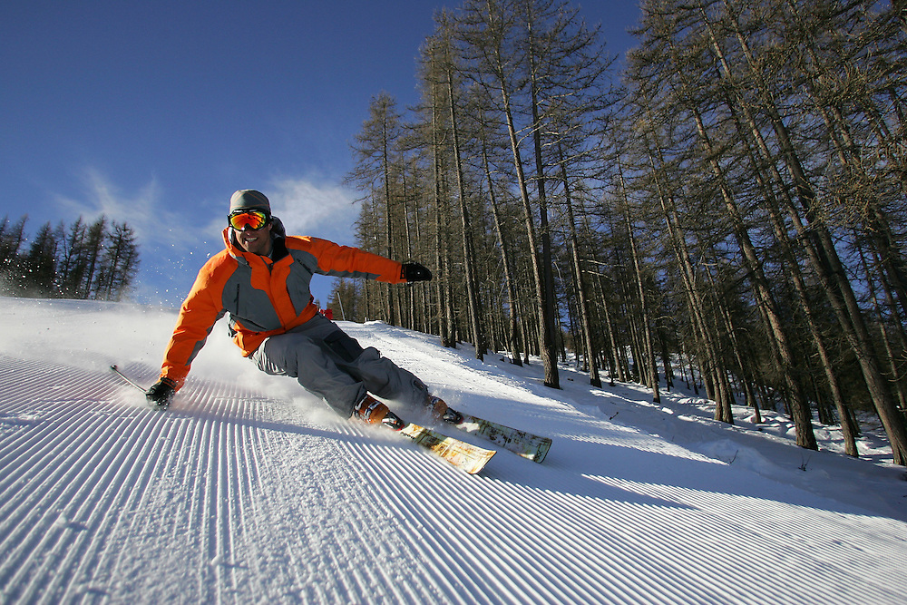 Sport. Male skier carve turns on freshly groomed ski piste. Serre Chevalier France