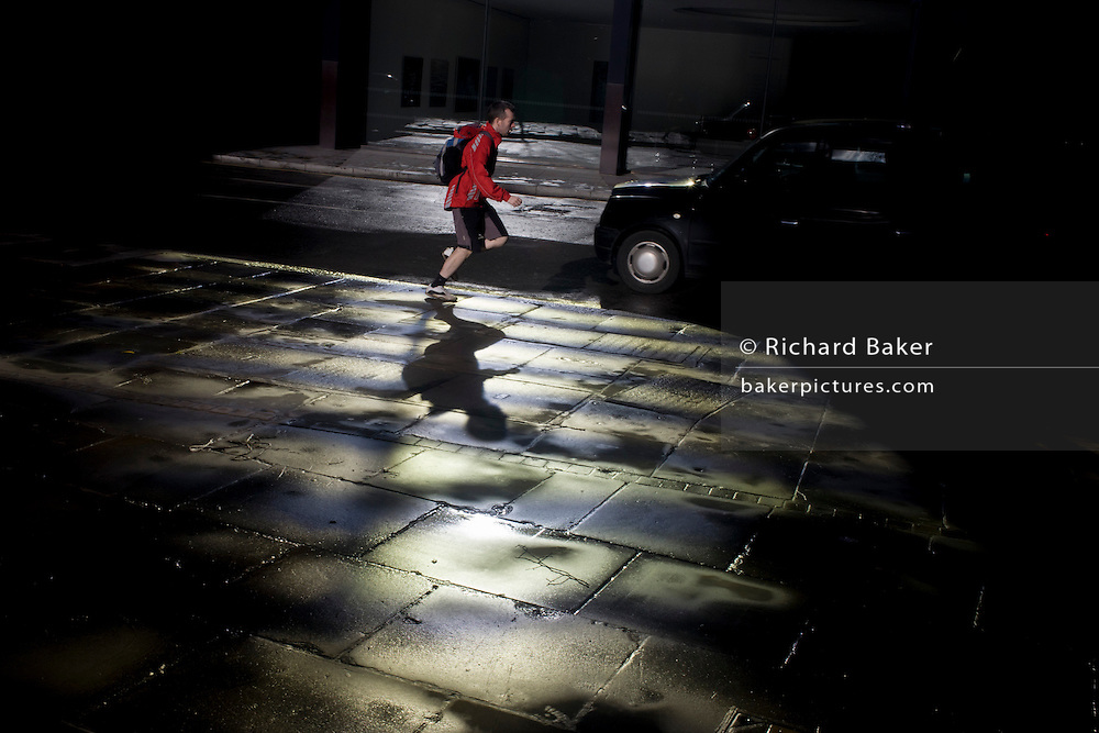 A runner passes-by a pool of bright reflective light in the heart of the financial City of London.