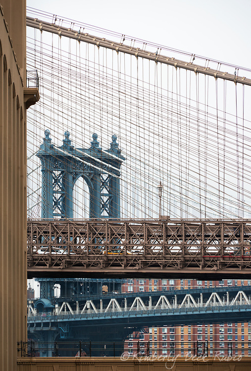 Manhattan Bridge, as seen through the cables of the Brooklyn Bridge, Brooklyn, New York.