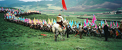 China, Hezhuo, 2005. A chain of riders stretches over the hills in a scene worthy of an epic film. Every August the Hezhuo Cultural Festival attracts thousands of Tibetans..