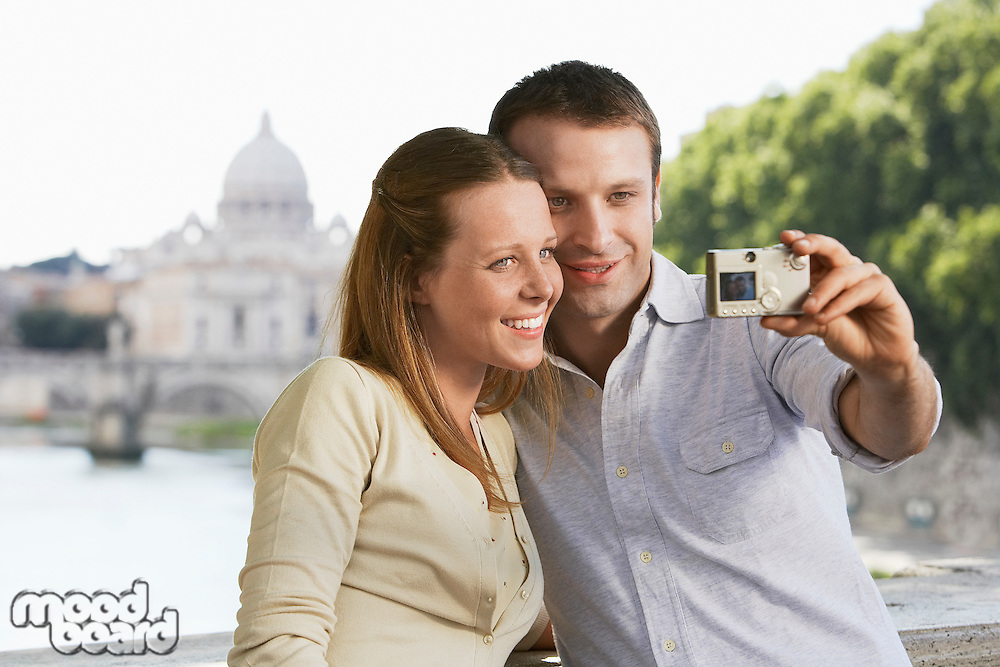 Couple photographing selves on bridge in Rome Italy front view