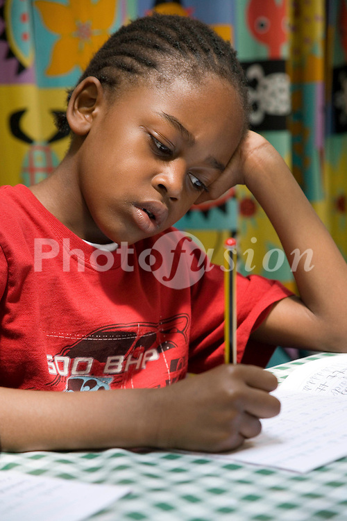 Boy sitting at desk in classroom working on maths problems,