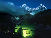 "A cooking tent glows green at dawn on a trek in the Cordillera Huayhuash, Andes Mountains, Peru, South America. Yerupaja Grande (left, east face, 6635 m or 21,770 ft) is the second-highest peak in Peru, highest in Cordillera Huayhuash, and highest point in the Amazon River watershed. At center is Yerupaja Chico (20,080 feet). On right is Mount Jirishanca (""Icy Beak of the Hummingbird,"" 6126 m or 20,098 feet). Published in Wilderness Travel Catalog of Adventures 2013. Published in ""Light Travel: Photography on the Go"" book by Tom Dempsey 2009, 2010."