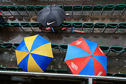 Spectators shelter under umbrellas as rain stops play during the ICC Women's World Cup match at Grace Road, Leicester.