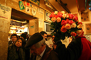 "A asian flower seller at ""Tasca do Chico"". This is one of the typical spots were to see live perfomances of Fado music and were the audience can spontaneously participate and also ask to sing. It is located in  Bairro Alto neighborhood"