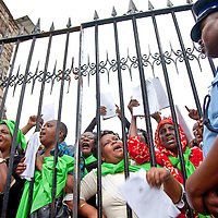 A police officer guards the gates of the Kenyan parliament as women activists demand access to their legislators in Nairobi, Kenya, Aug. 26, 2011. Hundreds of grassroots women leaders from across Kenya marched to Parliament on the eve of the country's one-year anniversary of the New Constitution to fight for women's rights to the promised one-third of Parliament seats. Currently, Kenya ranks 84th internationally for women in elected office with just nine percent women in parliament.