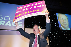 """© Licensed to London News Pictures . 25/05/2016 . Bolton , UK . NIGEL FARAGE waves a banner in the air at the end of his speech . Nigel Farage , Kate Hoey and Paul Nuttall at a """" We Want Our Country Back """" public meeting in favour of the UK leaving the EU at the Premier Suite of Bolton Wanderers' Macron Stadium . Photo credit : Joel Goodman/LNP"""
