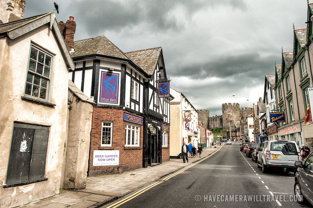 Shops on Castle Street, one of the main streets of Conwy that runs parallel to the waterfront. Conwy is an historic walled town most famous for Conwy Castle, which stands at the southern end of Castle Street and is visible in center-right of the frame.