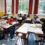 Nederland Rotterdam 23-09-2009 20090923 Serie over onderwijs,   openbare scholengemeenschap mavo, havo en vwo. Lesuur in klaslokaal, lerares geeft klassikaal  toelichting op de lesstof en stelt de leerlingen vragen.   , uitleggen, vaardigheden, vaardigheid, voor de klas staan, voortgezet, vrouw, young, zelfstandig werken                                            .Foto: David Rozing