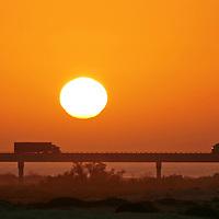 Trucks in silhouette on bridge at sunset