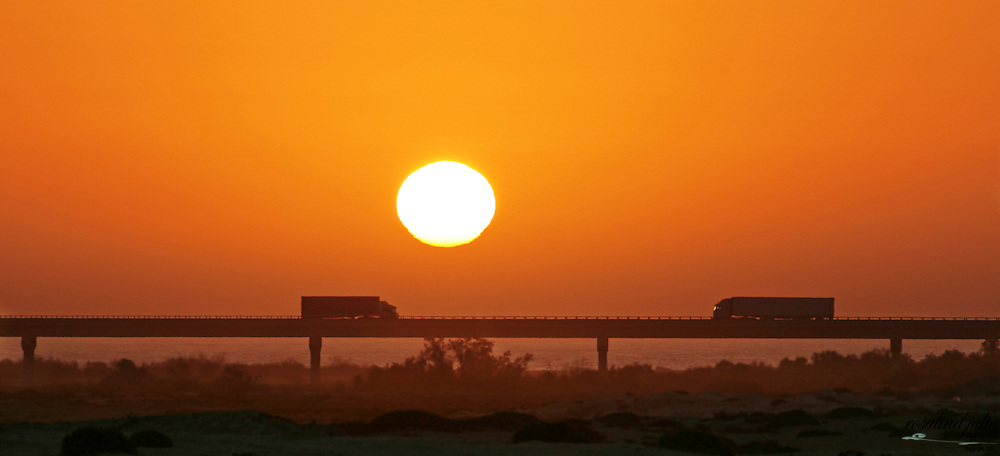 Trucks in silhouette on bridge at sunset