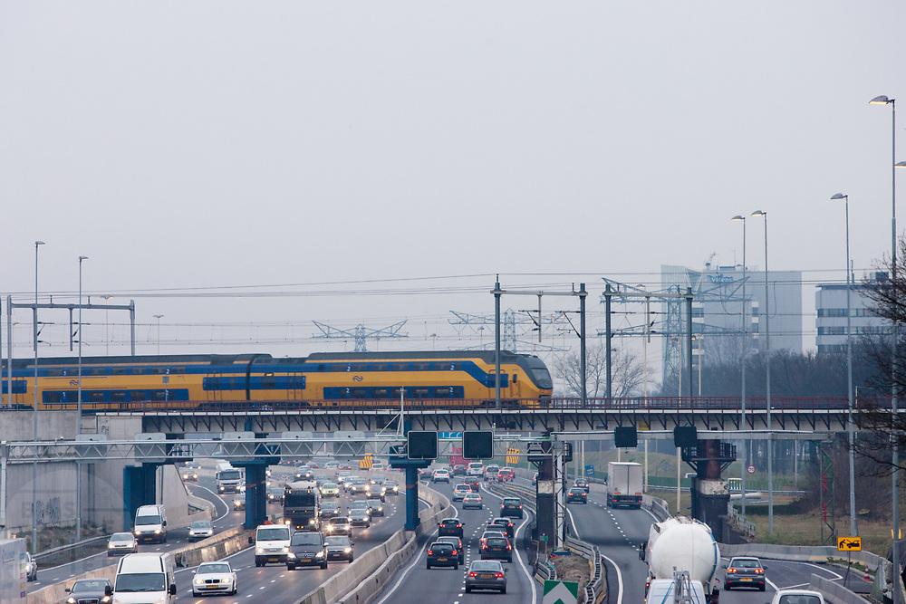 Verkeer raast langs de tunnel (uiterst links) bij de A2 in Utrecht, terwijl een trein bovenlangs rijdt. Het college van B en W in Utrecht heeft de vergunning verleent om de tunnel op de A2 open te stellen. Door meningsverschillen tussen de autoriteiten over de veiligheid was de tunnel nog steeds gesloten. Om de doorstroom te bevorderen was de snelweg tijdelijk met twee rijstroken verbreed voor 30 miljoen euro, de tunnel zelf heeft vijf rijstroken. De tunnel wordt gefaseerd in gebruik genomen, halverwege het jaar moet al het verkeer door de tunnel rijden.