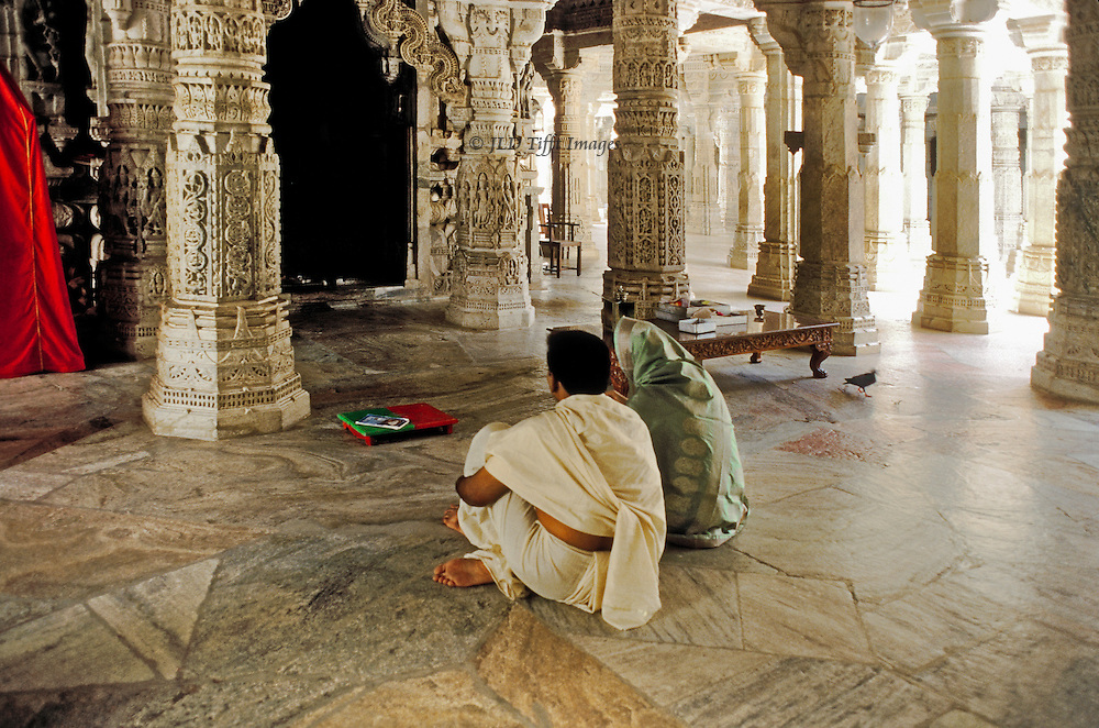 Man and woman seated together meditating on the cool marble floor of Ranakhpur, Jain temple built in 1439 in reign of Rana Kumbha, after businessman Dharma Sah dreamed that he should build a temple to Adinath, primary Jain deity, just at this spot.  Has 1444 columns each uniquely & richly carved with deities and floral motifs.  Beyond the couple, sunlight pours into an adjoining open courtyard.