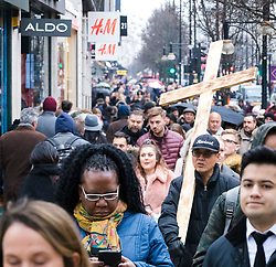 © Licensed to London News Pictures. 15/12/2018. London, UK.  A man carries a giant cross whilst Christmas shopping in Oxford Street in London today, less than two weeks before Christmas on what is usually one of the busiest shopping weekends of the year.  Photo credit: Vickie Flores/LNP