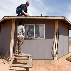 032713     Brian Leddy<br /> Dough Vilsack, Keyvan Izadi and Rachel Jones install a small solar panel on the roof of Alice Dougi's home near Bodaway Gap Wednesday, March 27.