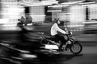 Man riding motorbike in the blur of Saigon traffic at night.
