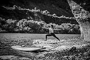 Woman Stand Up Paddle Boarding does yoga on the shore of the the Snake River in the canyon in Twin Falls, Idaho. MR