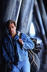 good looking man in denim with a large sack over his shoulder while standing under a pier in Santa Monica, CA
