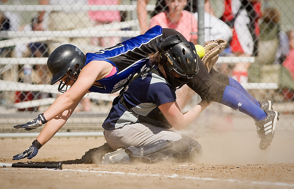 JEROME A. POLLOS/Press..Bear Lake's Abby Hardcastle goes up and over Timberlake catcher Natasha Palmer during Friday's 3A state softball tournament at Ramsey Park. Hardcastle was safe after Palmer lost the ball in the collision.