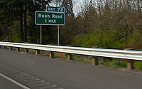 scene along a cross country trip with in a classic Mini Cooper auto - road sign for Rush Road I-5 exit tells the story of the road trip