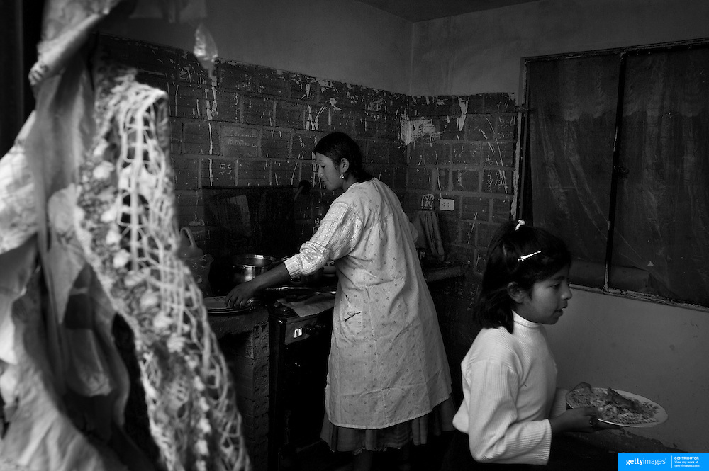 Cholita wrestler Yolanda La Amorosa  with her daughter Adriana during meal time at her home in La Paz. Yolanda is part of the 'Titans of the Ring' wrestling group who perform every  Sunday at El Alto's Multifunctional Centre. Bolivia. The wrestling group includes the fighting Cholitas, a group of Indigenous Female Lucha Libra wrestlers who fight the men as well as each other for just a few dollars appearance money. El Alto, Bolivia, 24th March 2010.