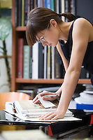 Young designer leans forward researching a book