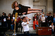 """A young magician performs a levitation trick using a lady assistant, in front of a crowd in Covent Garden's Piazza, London. Saying abracadabra or a similar explanation to wow his surrounding audience, the man stands beneath the raised woman, lying horizontally in mid-air. Levitation (from Latin levitas """"lightness"""") is the process by which an object is suspended by a physical force against gravity, in a stable position without solid physical contact."""