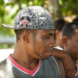 Portrait of a young papua wearing a baseball cap.