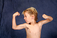 Young boy flexing his muscles. Caucasian kid showing strength.