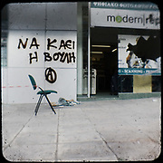 A broken shop in Alexandras avenue, Athens. The graffiti writes: &ldquo;Burn the parliament&rdquo; <br /> <br /> Following the murder of a 15 year old boy, Alexandros Grigoropoulos, by a policeman on 6 December 2008 widespread riots, protests and unrest followed lasting for several weeks and spreading beyond the capital and even overseas<br /> <br /> When I walked in the streets of my town the day after the riots I instantly forgot the image I had about Athens, that of a bustling, peaceful, energetic metropolis and in my mind came the old photographs from WWII, the civil war and the students uprising against the dictatorship. <br /> <br /> Thus I decided not to turn my digital camera straight to the destroyed buildings but to photograph through an old camera that worked as a filter, a barrier between me and the city.